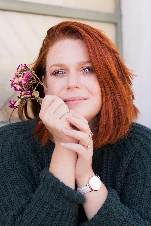 Cheveux roux et yeux bleus, pull vert sapin, make-up réalisé avec la palette Soft Glam d'Anastasia Beverly Hills des fleurs séchées roses dans les mains