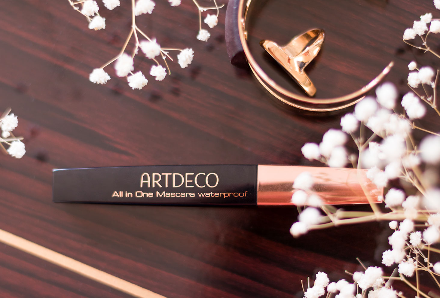 Le mascara waterproof de ARTDECO vu de haut, posé sur une table en bois foncé, au milieu des bijoux dorés et des fleurs séchées