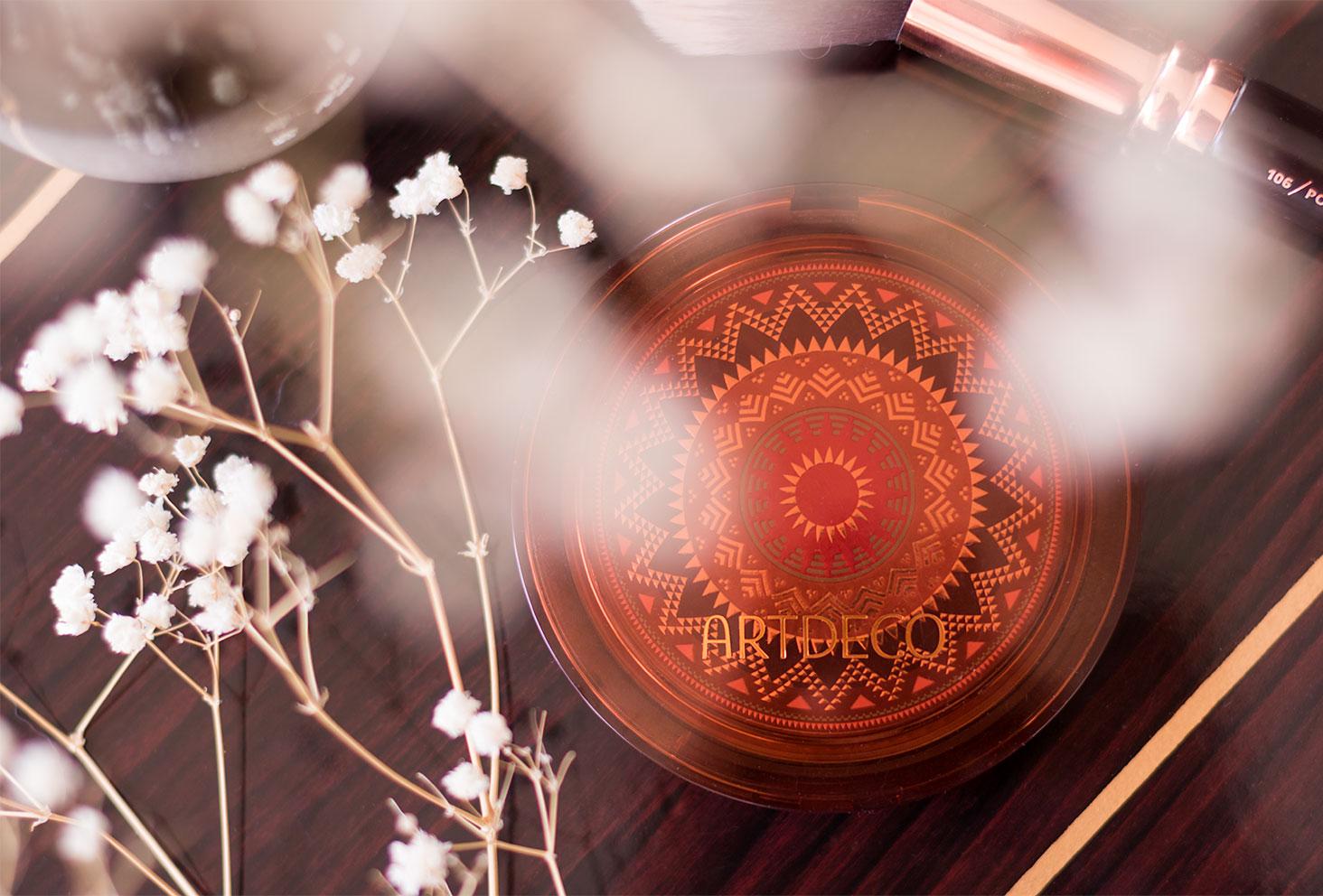 La poudre bronzante ARTDECO fermée vu de haut, posée sur une table vernis en bois au milieu des fleurs séchées