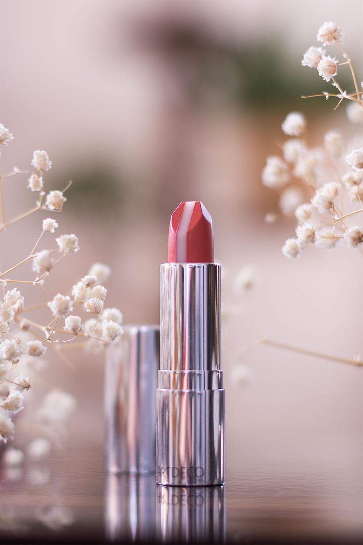 Le rouge à lèvres ARTDECO ouvert, posé debout sur une table en bois au milieu des fleurs séchées