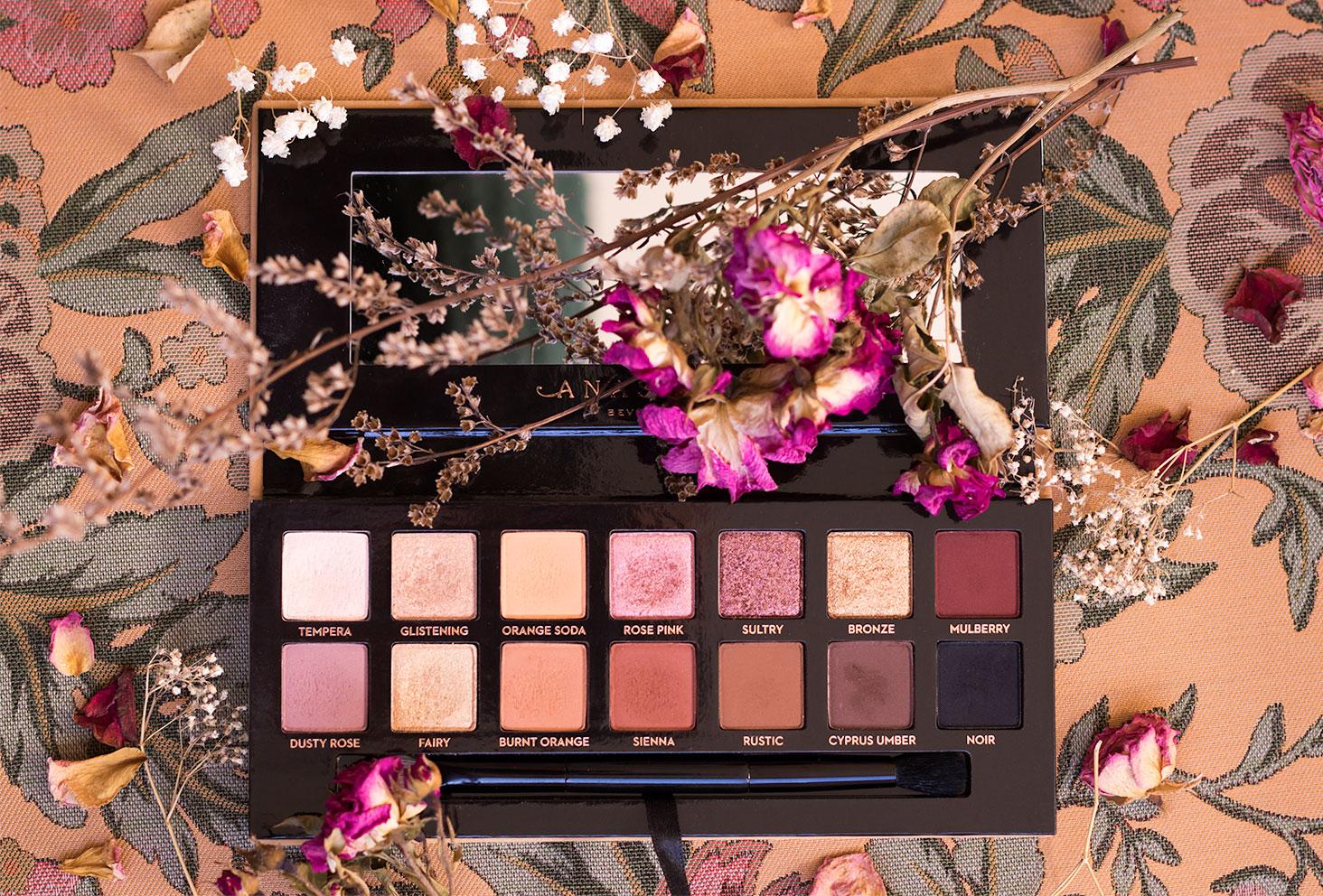 Zoom sur la palette Soft Glam d'Anastasia Beverly Hills, posée sur un vieux tissu fleurit au milieu des fleurs séchées
