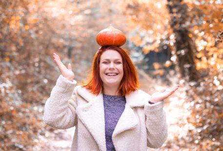 Potimarron dur la tête en équilibre, le sourire jusqu'aux oreilles, au milieu de la forêt d'automne