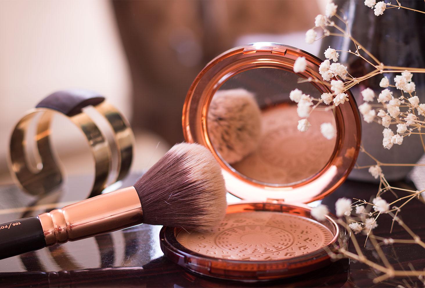 La poudre bronzante ARTDECO posé sur une table en bois au milieu des fleurs séchées, ouverte avec un gros pinceau à l'intérieur