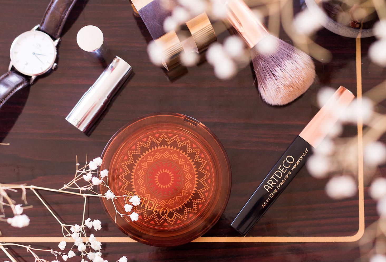 La poudre bronzante, le rouge à lèvres et le mascara ARTDECO vu de haut, posés sur une table en bois vernis au milieu des pinceaux et fleurs sèches