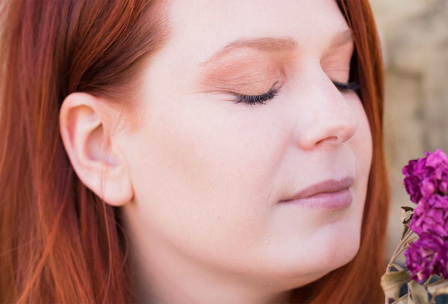 Zoom sur le make-up nude réalisé avec la palette Soft Glam, les yeux fermés et des fleurs sèches violettes près du visage