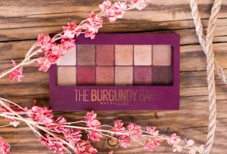 La palette The Burgundy Bar de haut fermée, sur une table en bois, au milieu de cordages et de fleurs sèches roses