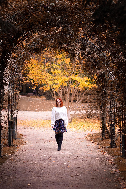 Au milieu d'une arche recouverte de feuilles aux couleurs de l'automne, en jupe et pull blanc
