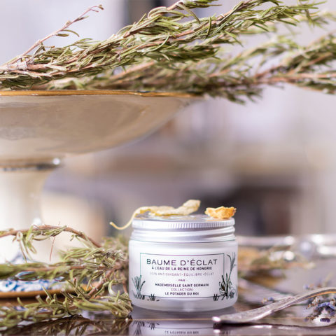 Le baume d'Eclat de Mademoiselle Saint Germain au milieu des fleurs sèches, du romarin et des couverts en argent, sur une desserte en bois vernis à liseré doré