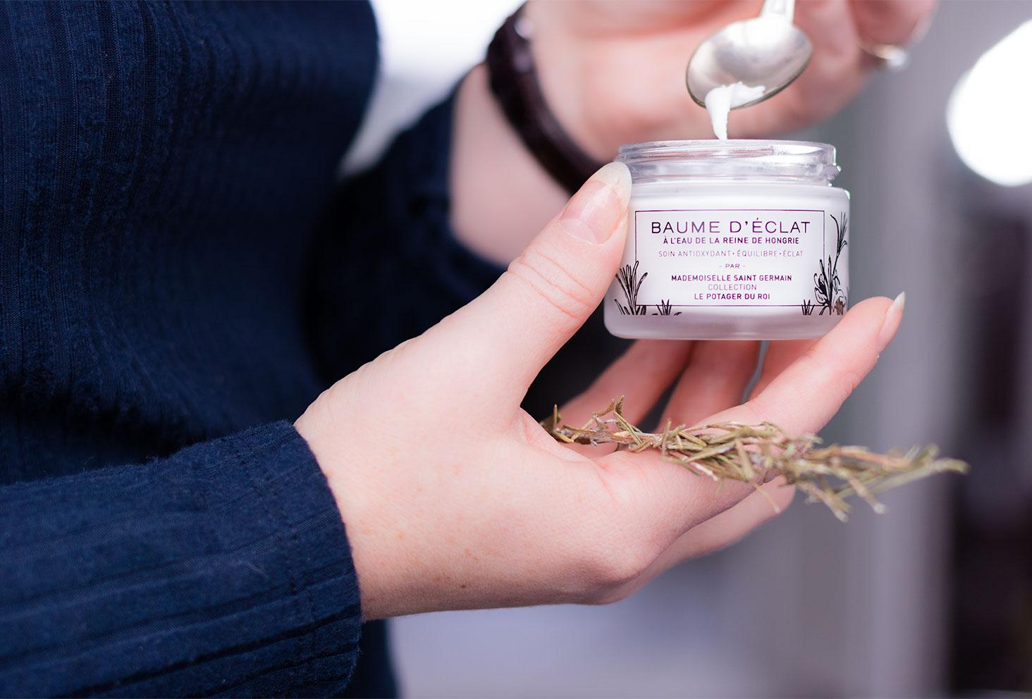 La texture du baume d'Eclat de Mademoiselle Saint Germain dans une petite cuillère en argent, le pot tenu comme un yaourt dans la main