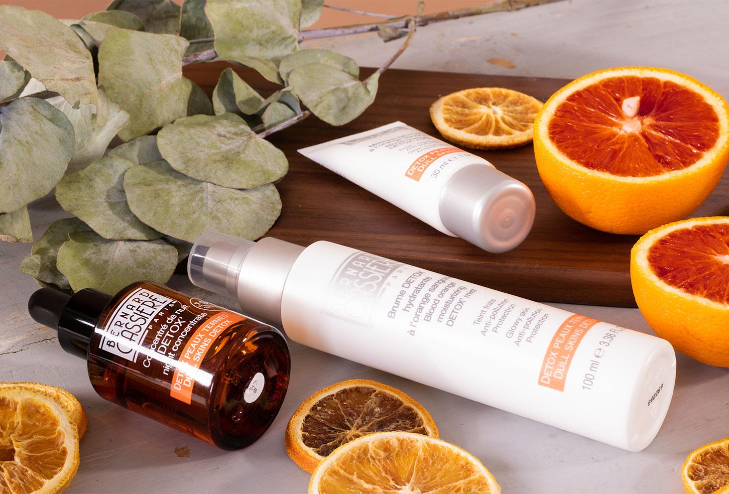 Le concentré de nuit, la brume et le masque de la gamma détox à l'orange sanguine de Bernard Cassière sur une table grise, couché au milieu des oranges sanguines