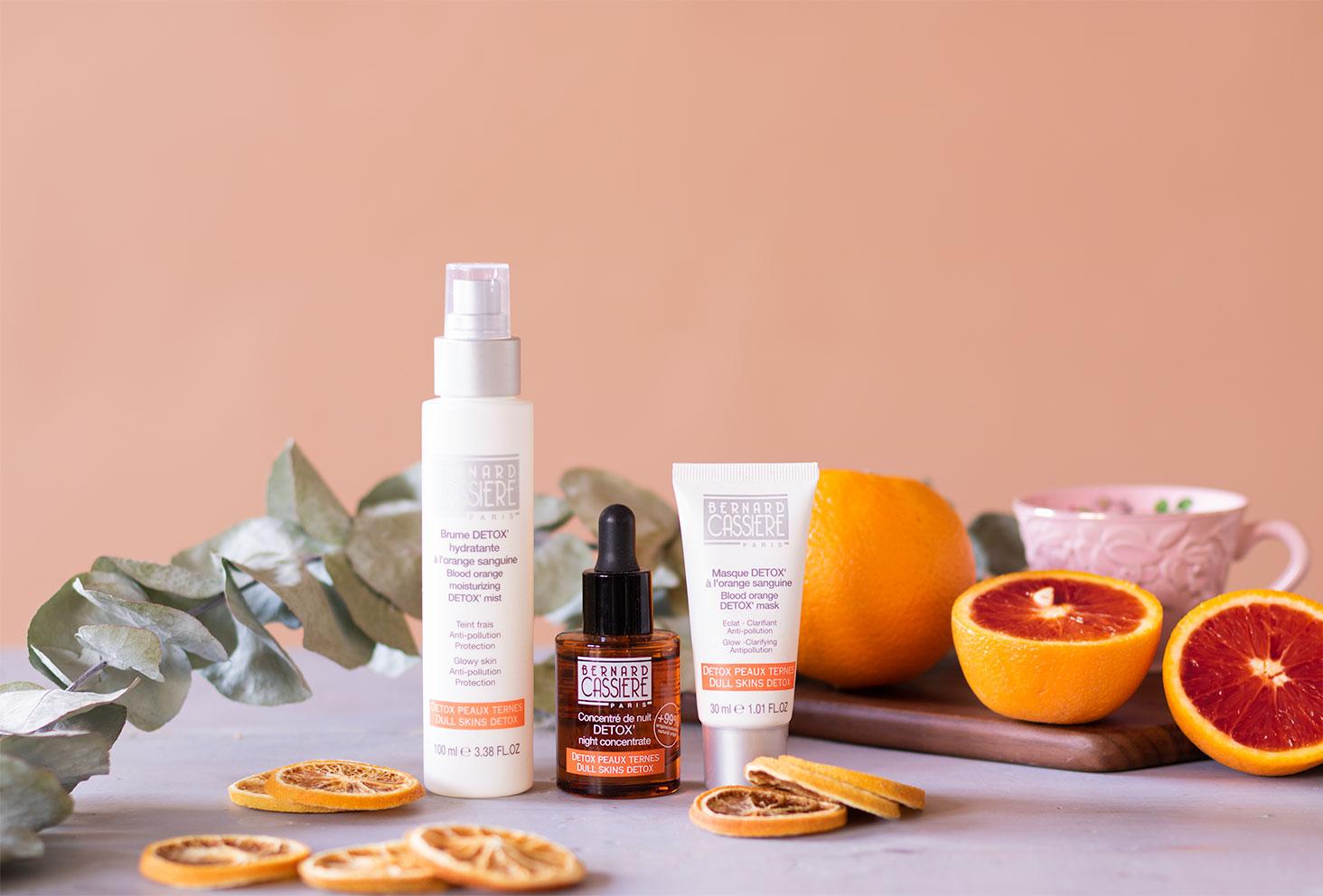 La gamme détox à l'orange sanguine de Bernard Cassière sur une table grise, devant une planche en bois dans l'esprit du thé anglais, au milieu des oranges sanguines et d'une branche d'eucalyptus séchée