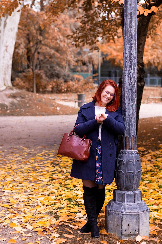 En train de regarder l'heure appuyé contre un vieux lampadaire dans un parc aux couleurs de l'automne, en manteau bleu et cuissardes