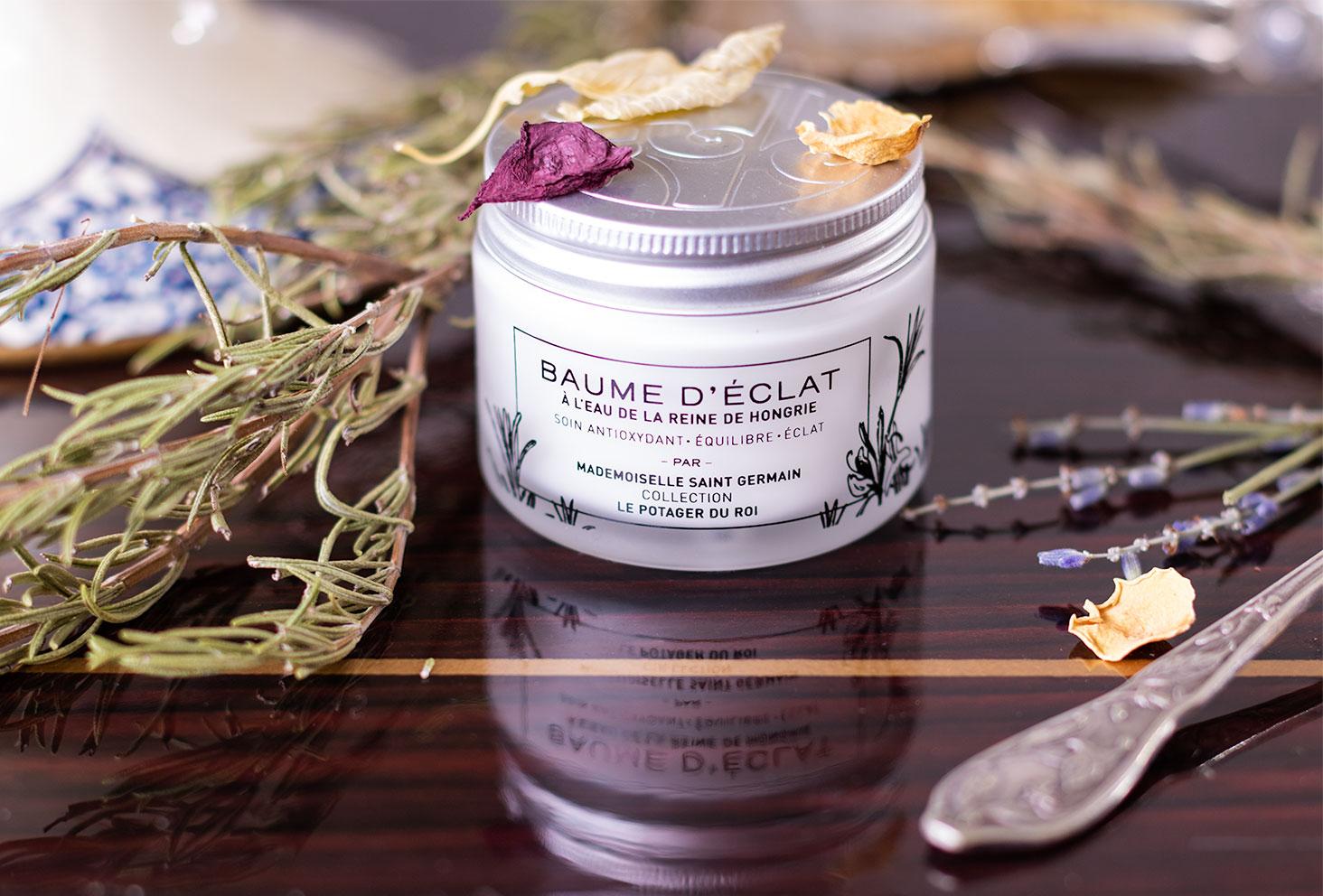 Zoom sur le pot du baume d'Eclat au romarin de Mademoiselle Saint Germain sur une desserte en bois vernis au milieu de fleurs sèches et de romarin sec à la douce odeur