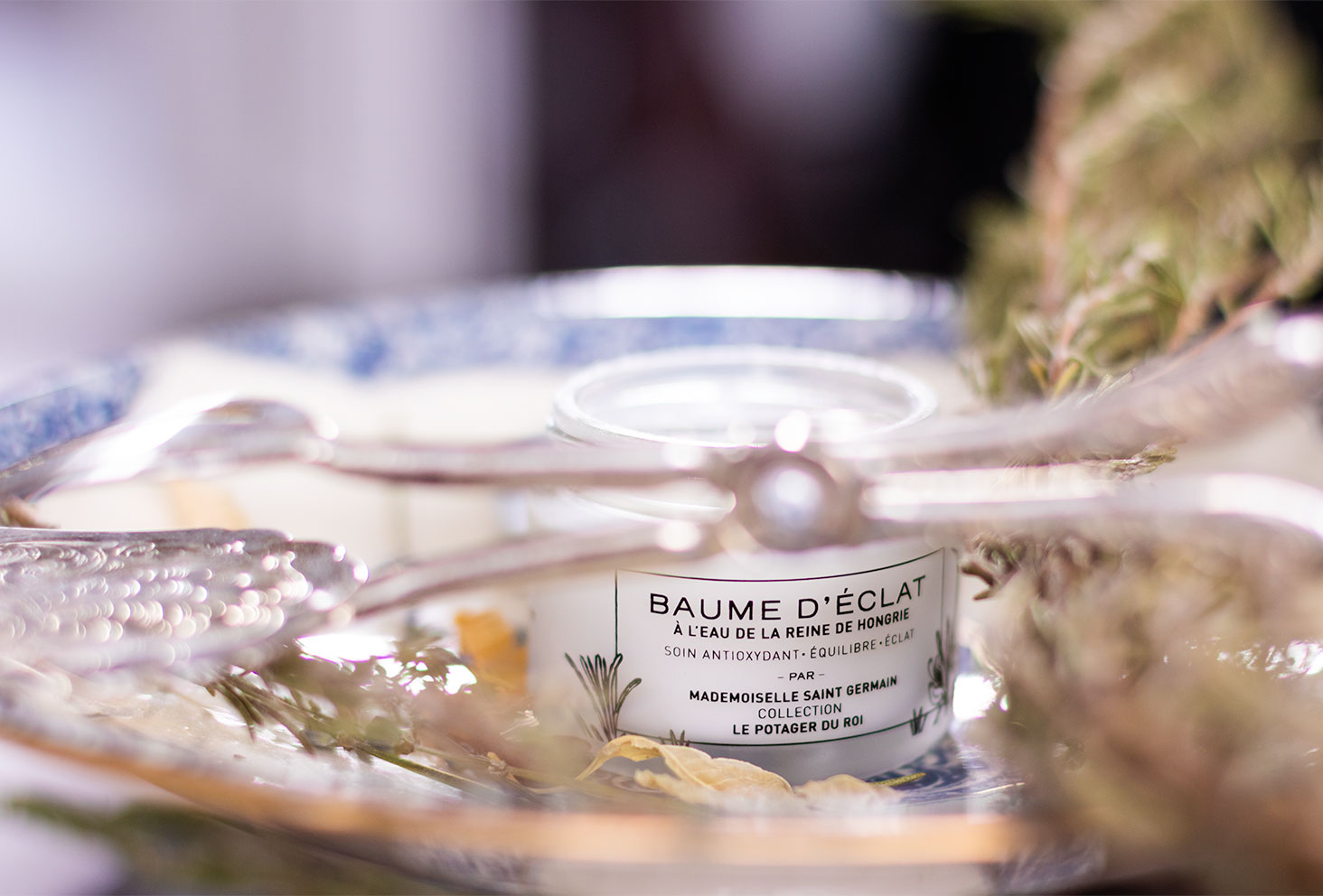 Le pot du baume d'Eclat à l'eau de la Reine de Hongrie pour la routine visage idéale de l'hiver, dans une soucoupe en porcelaine, au milieu du romarin et des couverts en argent