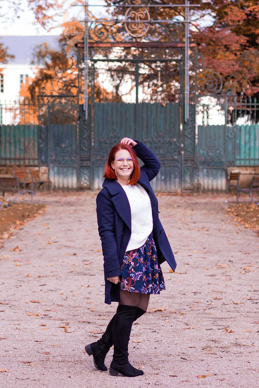 Devant un portail en métal, au milieu d'une allée d'automne, en look d'huver et cuissardes noires