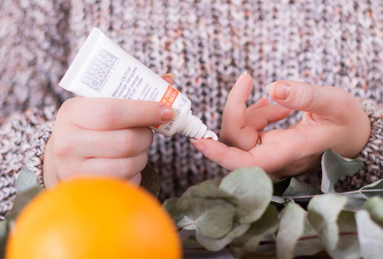 Zoom sur la texture du masque détox à l'orange sanguine de Bernard Cassière sur le bout du doigt de face au milieu des oranges et de l'eucalyptus