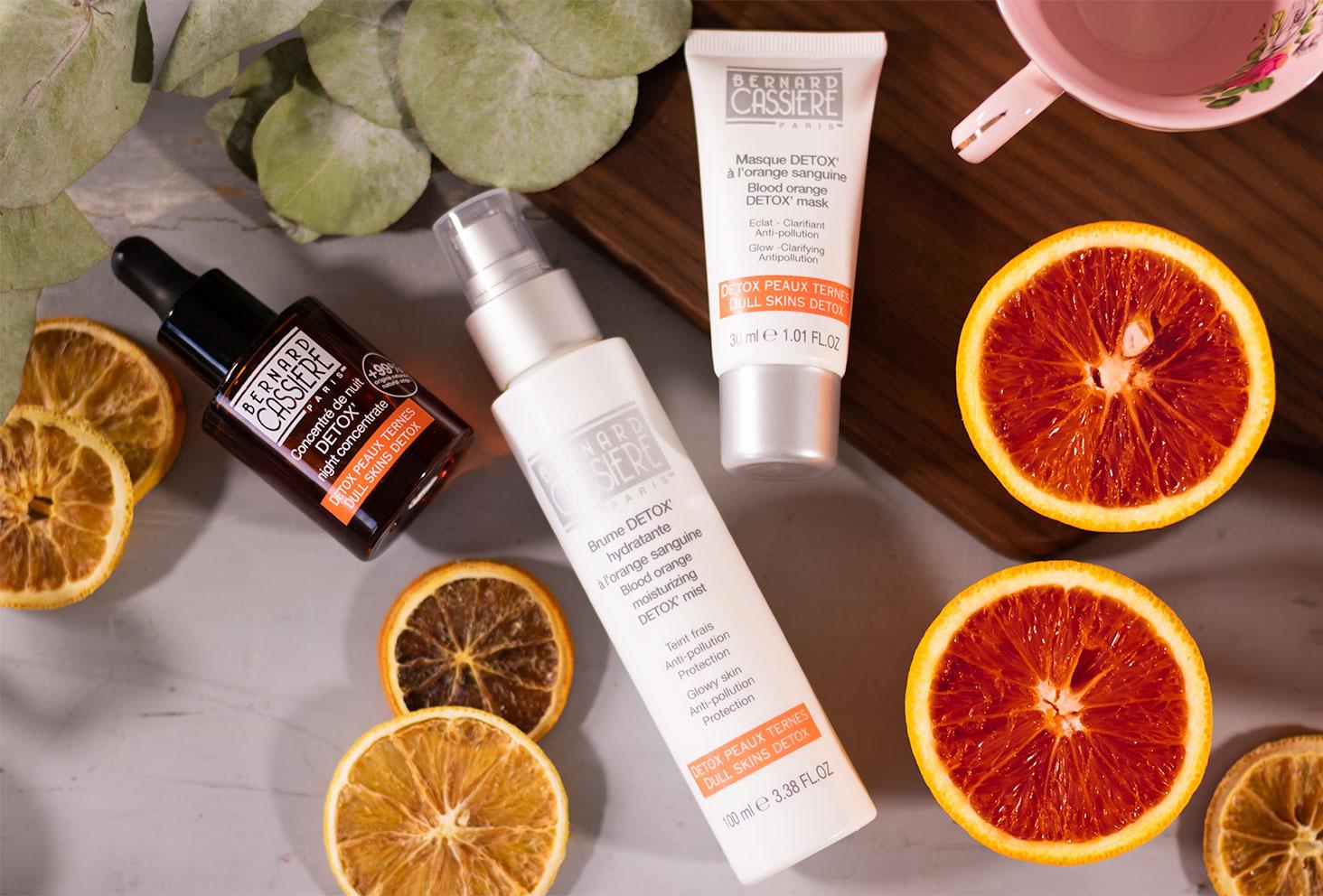 Les produits détox à l'orange sanguine de Bernard Cassière posé sur une planche en bois et sur une table grise au milieu des oranges sanguines