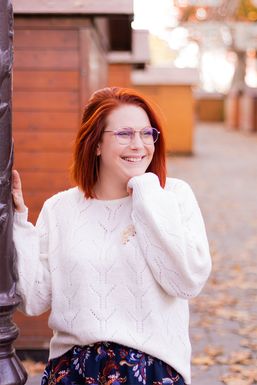 La main sur le lampadaire devant les cabanes du marché de Noël, en pull oversize blanc et jupe bleue marine à fleurs