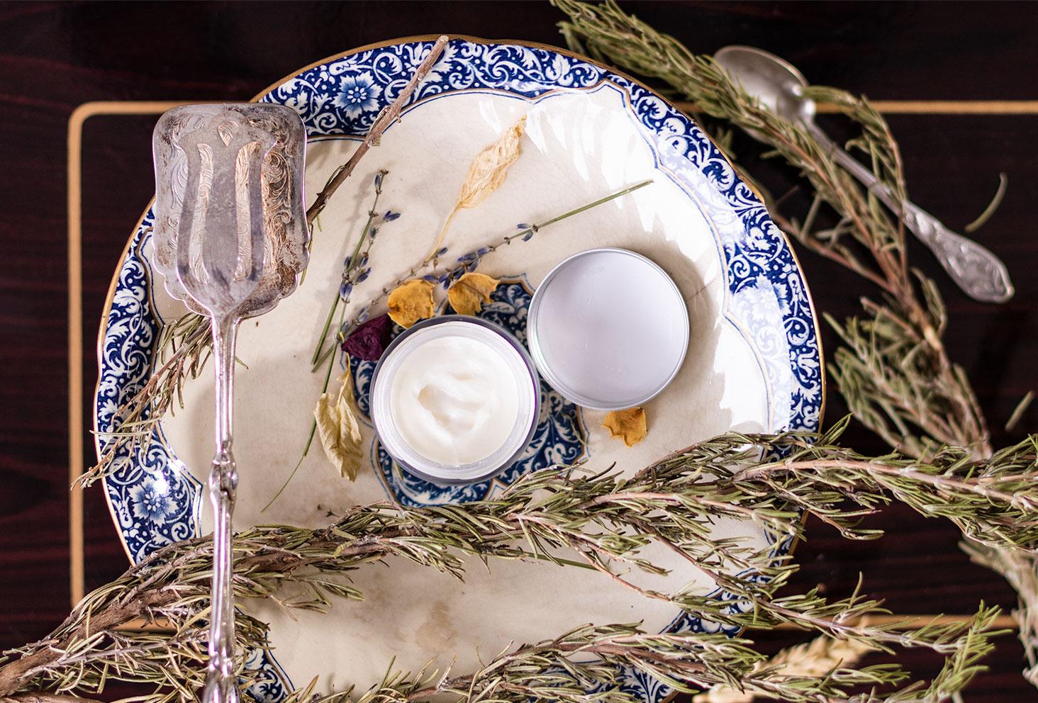 Le pot du baume d'Eclat de Mademoiselle Saint Germain ouvert, au milieu de couverts en argent sur une desserte en bois vernis
