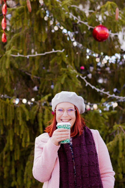 Devant un sapin décoré pour Noël, en manteau rose et béret gris, avec un café Starbucks de Noël dans les mains