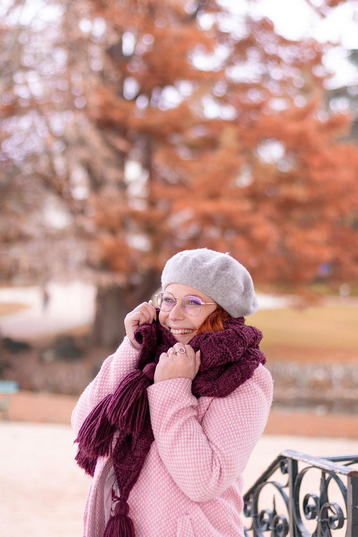 Emmitouflée dans une grosse écharpe bordeaux en laine avec un manteau rose et un béret gris sur la tête, au milieu d'un parc aux couleurs automnales