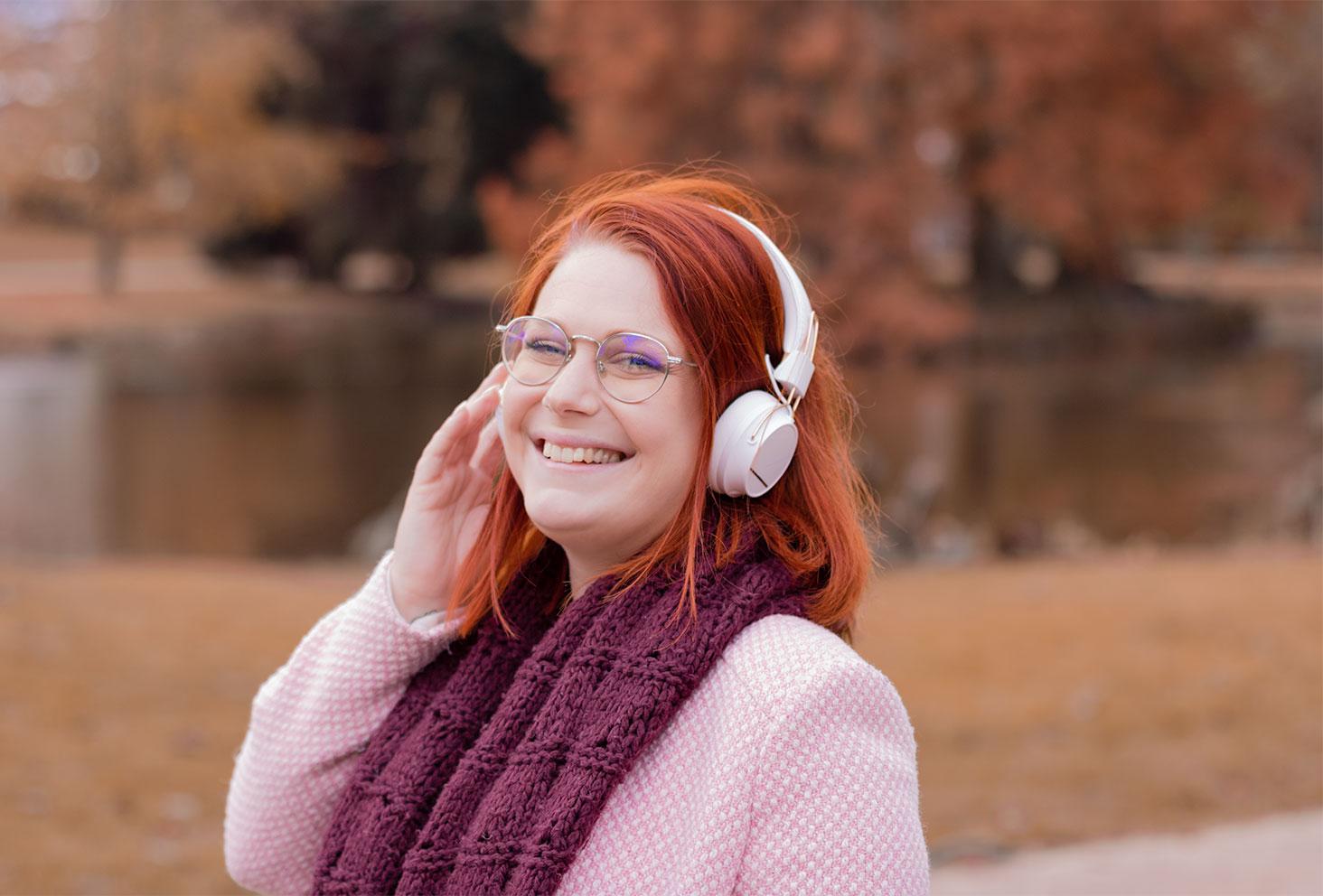 Au milieu d'un parc aux couleurs de l'automne, en manteau rose et écharpe en laine bordeaux, un casque blanc sans fils SUDIO sur les oreilles