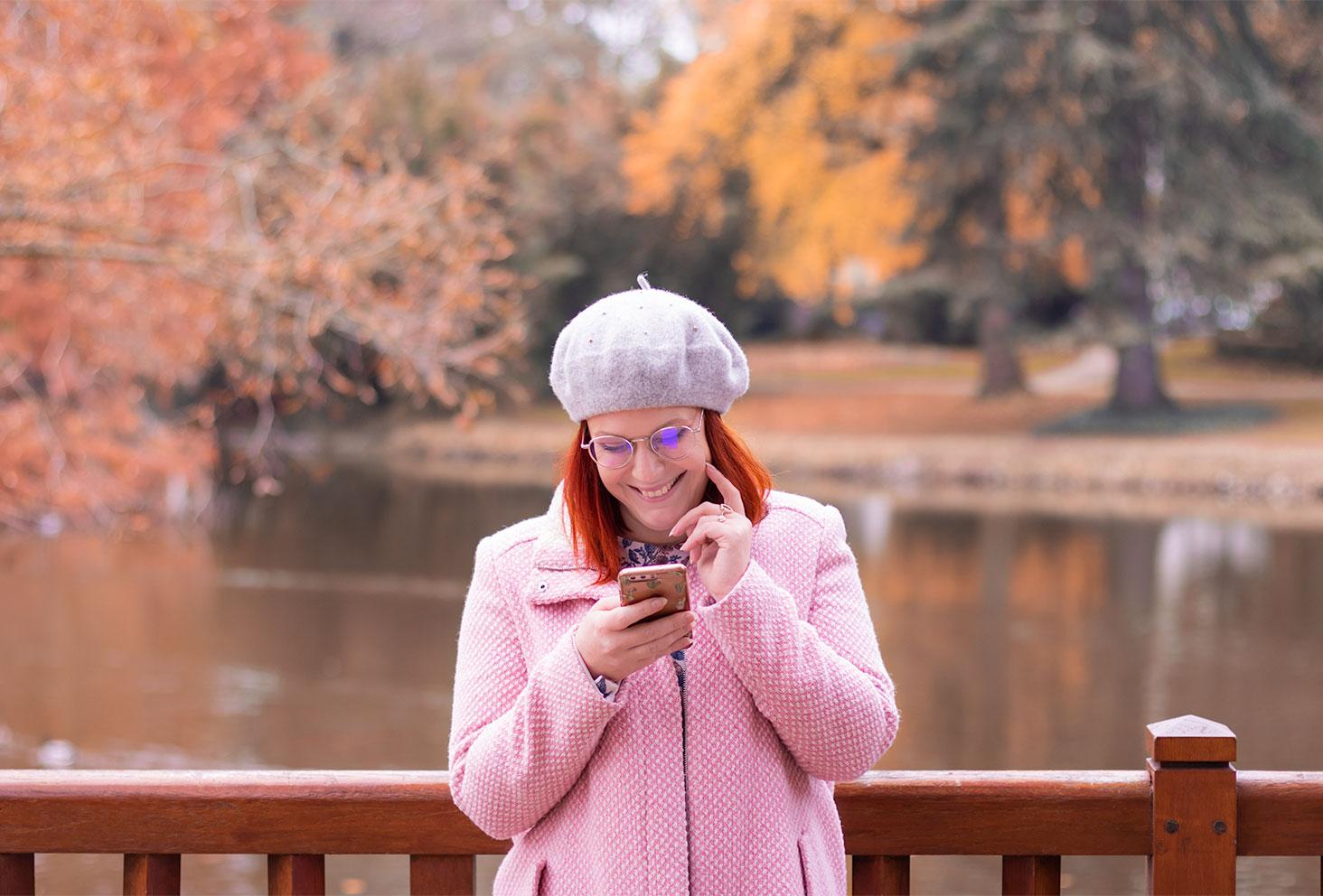 Appuyée le long d'une rambarde en bois au dessus d'un pont au milieu des couleurs d'automne, en manteau rose avec un béret gris sur la tête, le téléphone dans les mains