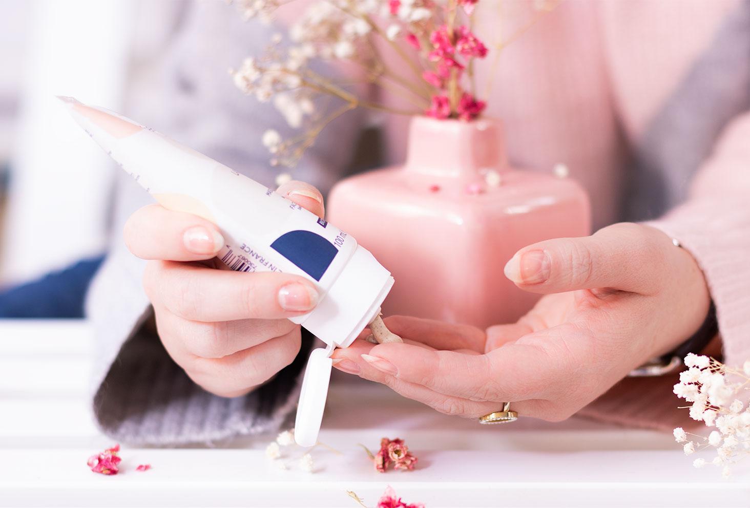 Utilisation du masque & gommage de Gallinée dans les mains, au dessus d'une étagère blanche devant le vase rose de fleurs sèches
