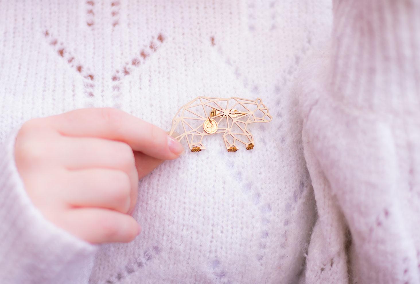 Zoom sur la broche dorée ours de Petite Cassiopeia portée sur un pull en laine blanc