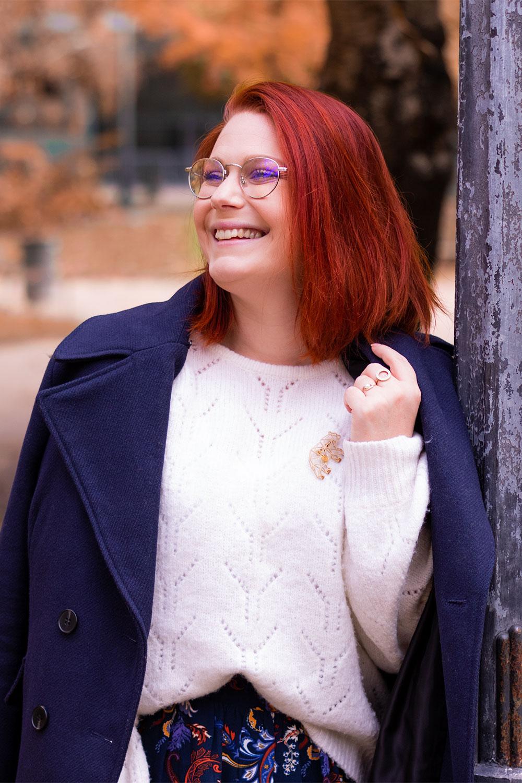 Appuyée contre un lampadaire, le manteau bleu Kiabi sur les épaules en pull blanc loose
