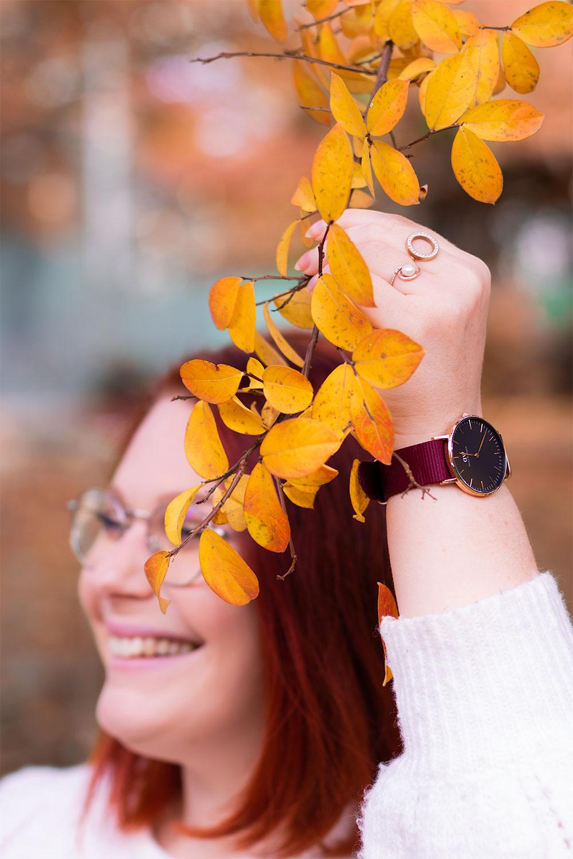 Zoom sur la montre Daniel Wellington portée au milieu des feuilles jaunes d'automne d'un arbre