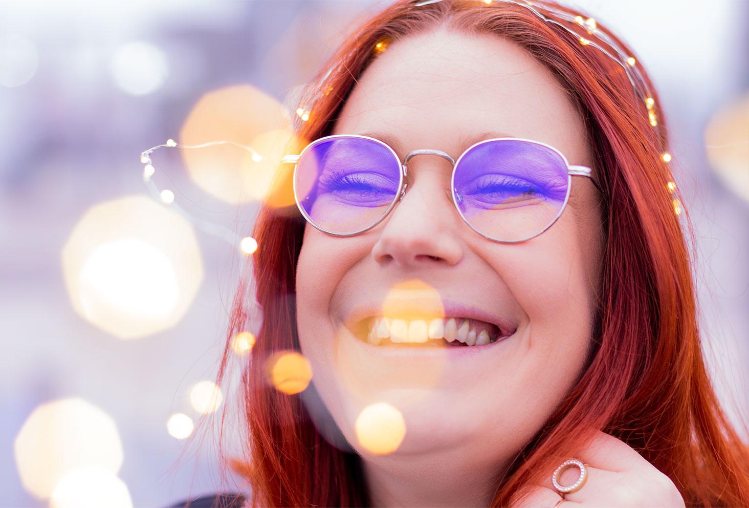 Grand sourire et lunettes aviators, une guirlande sur la tête pour la nouvelle année