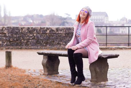 Assise sur un banc devant le château d'amboise dans la brume, en train de remettre les cuissardes en place, en manteau rose et robe à fleurs roses