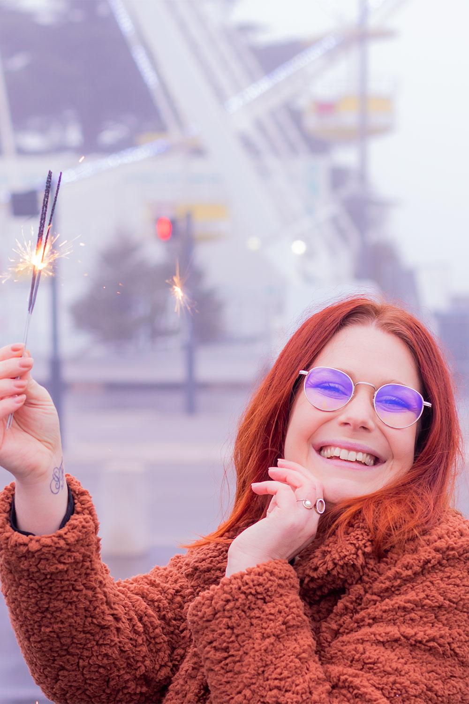 En manteau moumoute devant une grande roue illuminée, des bougies magiques allumées dans la main