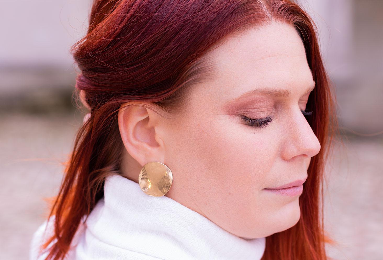 De profil, zoom sur des boucles d'oreilles rondes et dorée de SheIn