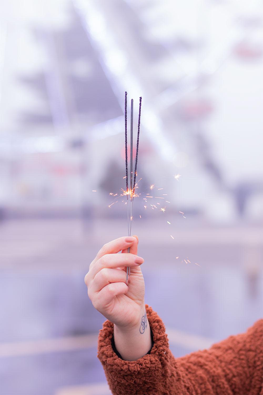 Zoom sur des bougies cierges magiques allumées dans une main, devant une grande roue illuminée