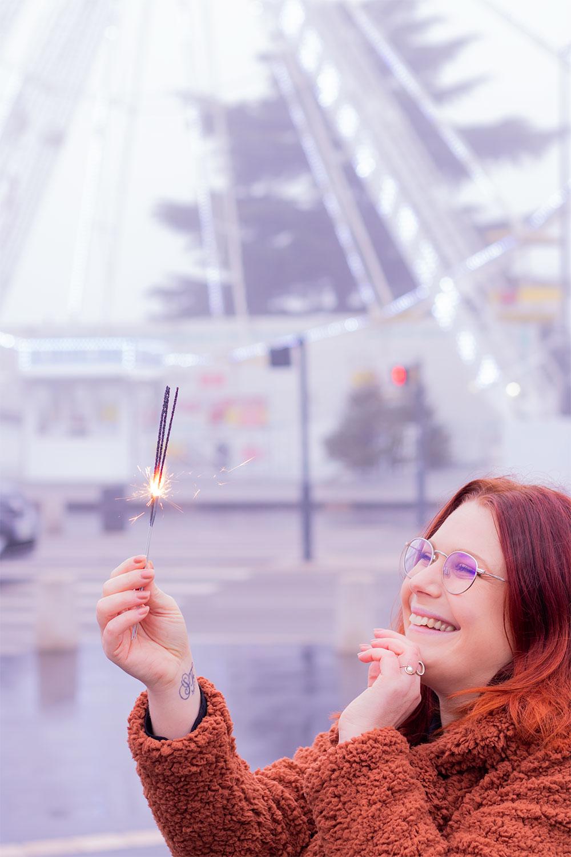 Des cierges magiques allumés dans les mains, devant la grande roue illuminée, pour fêter la nouvelle année