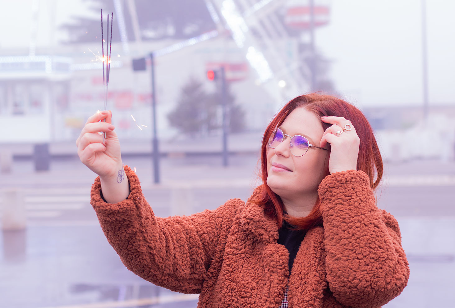 Devant des cierges magiques allumés pour fêter la nouvelle année, une main dans les cheveux en manteau moumoute