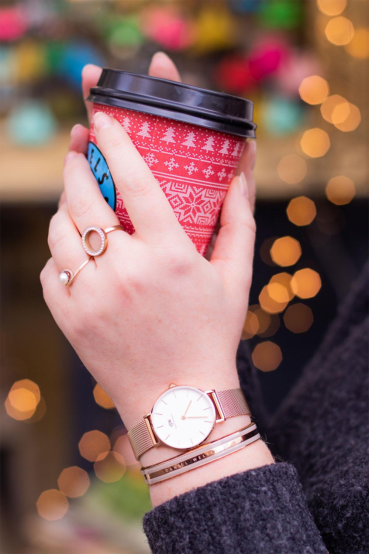 La montre Classic petite Melrose portée avec le Classic Bracelet de Daniel Wellington, un mug de Noël dans les mains devant les lumières des guirlandes de Noël