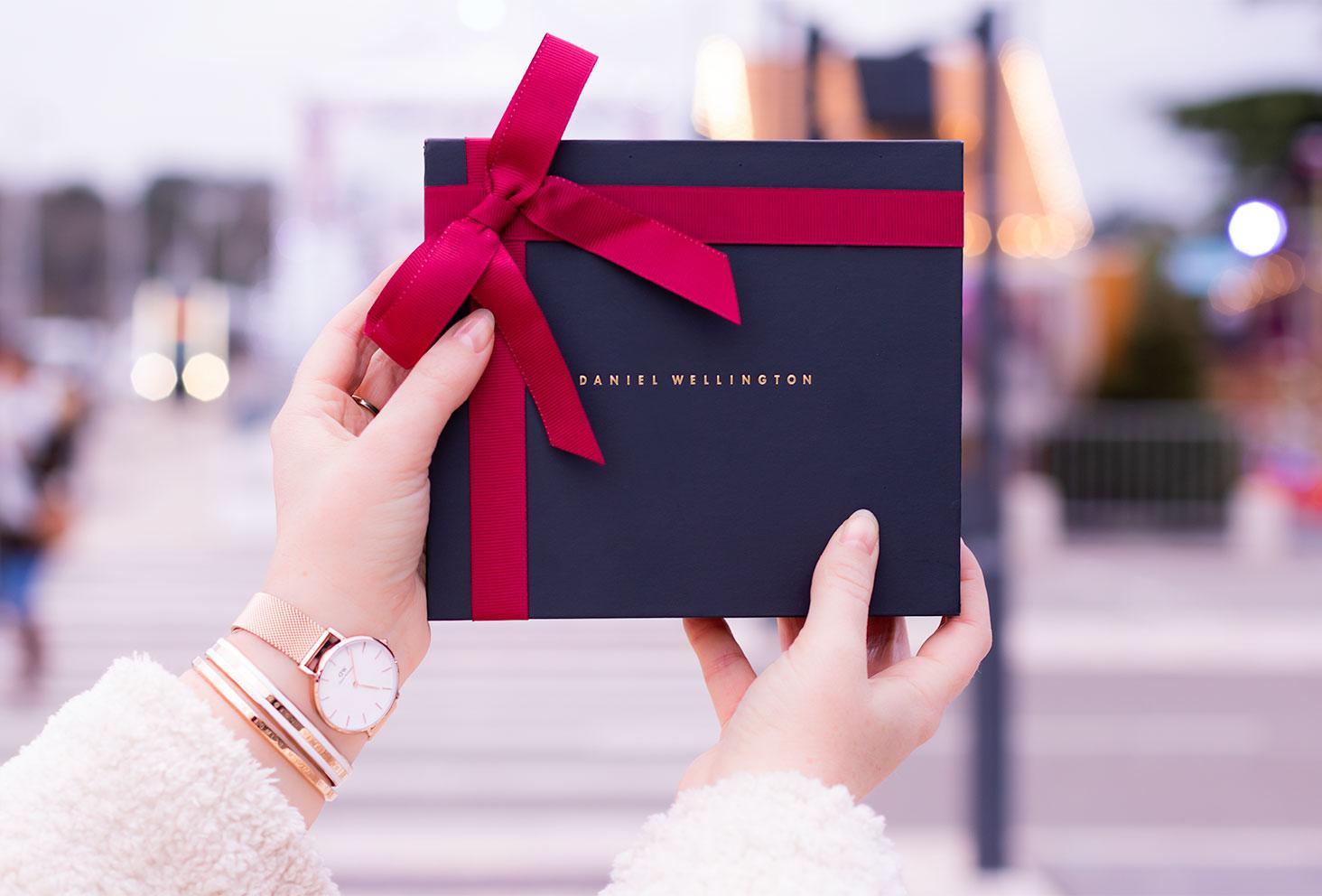 Un coffret cadeau Daniel Wellington tenu entre les mains au milieu des lumières de Noël en pleine ville, la montre Classic petite Melrose portée au poignet