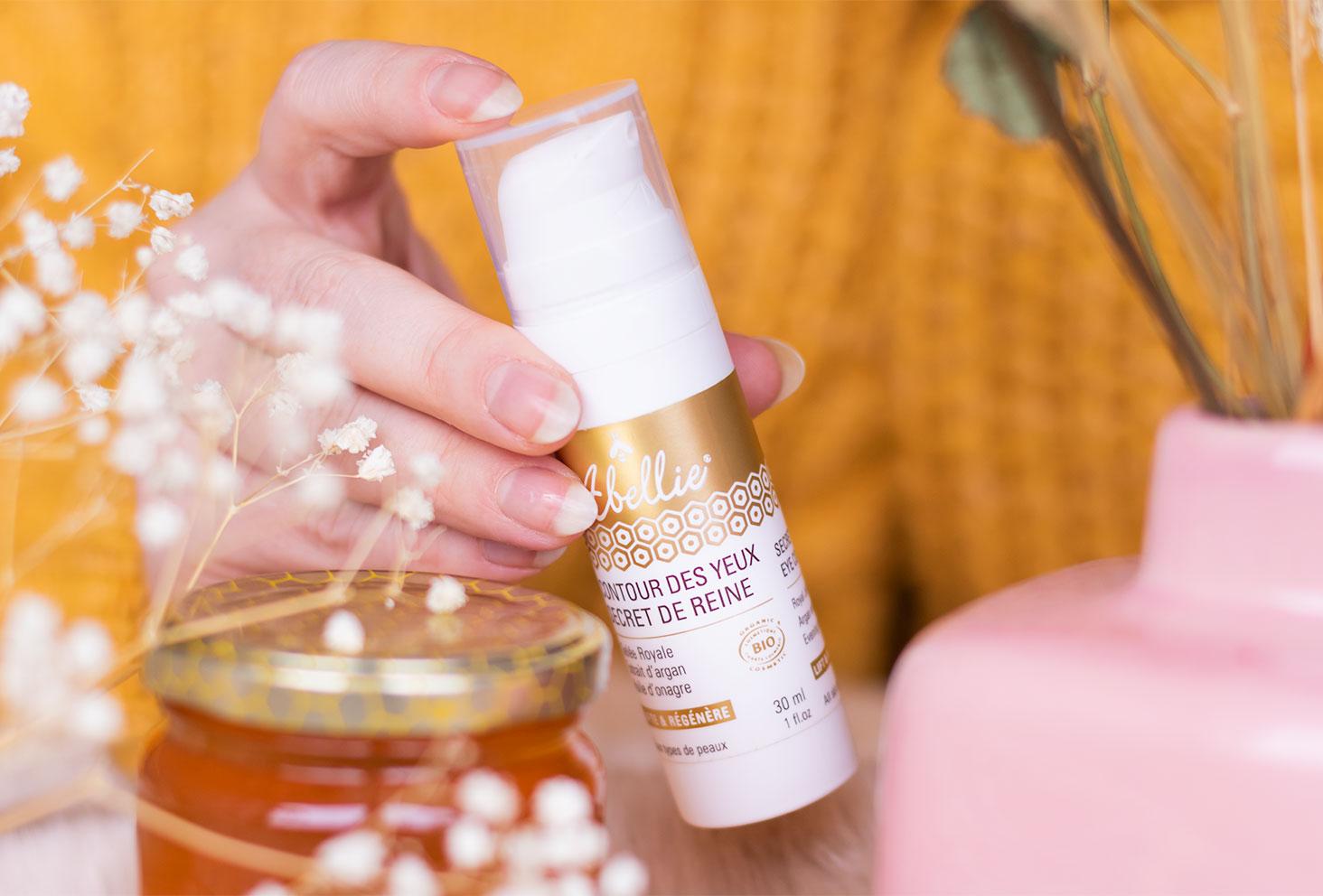 Zoom sur le contour des yeux Abellie, tenu dans la main au milieu de fleurs sèches et de miel