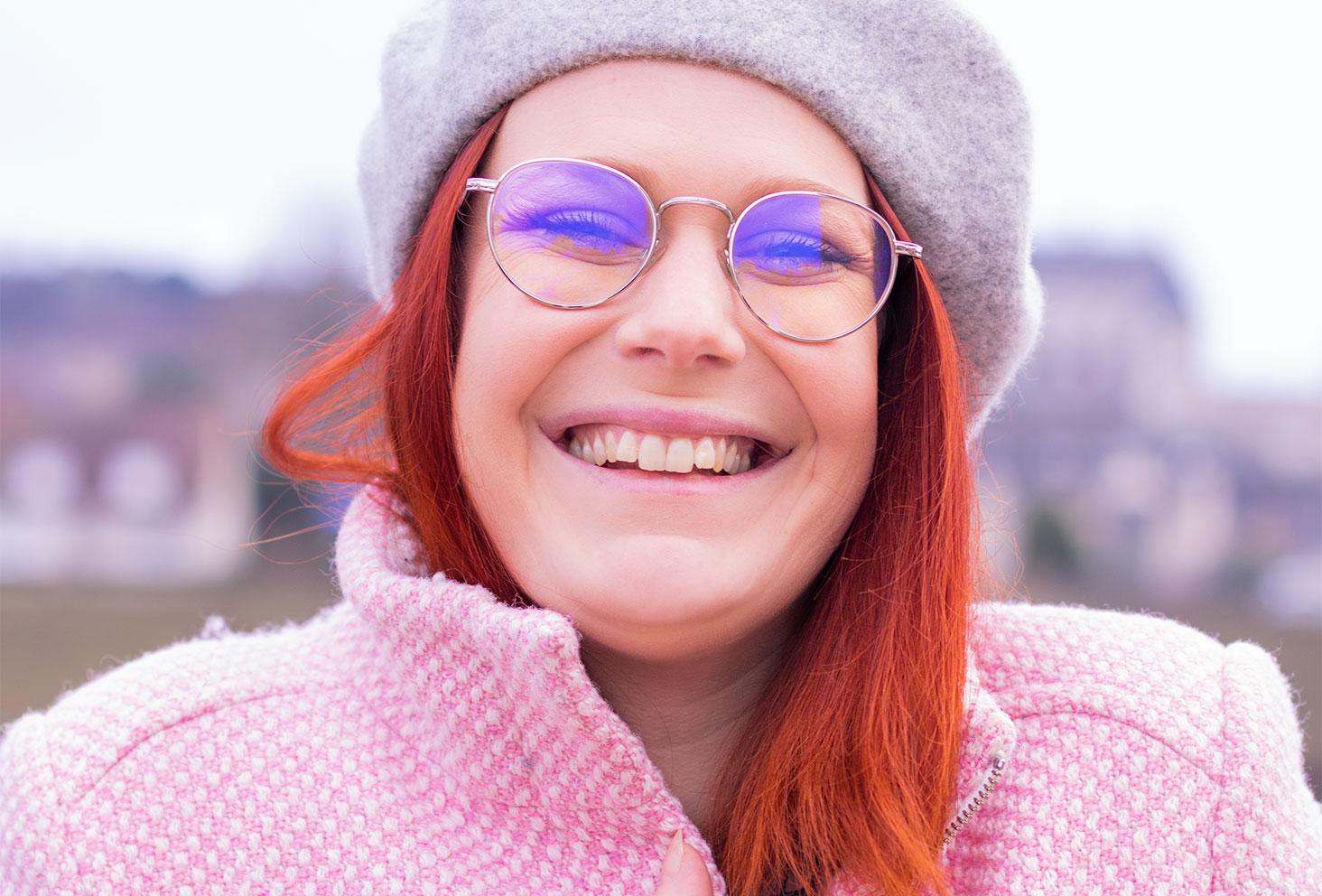 Zoom devant le château d'Amboise en manteau rose et béret gris sur la tête