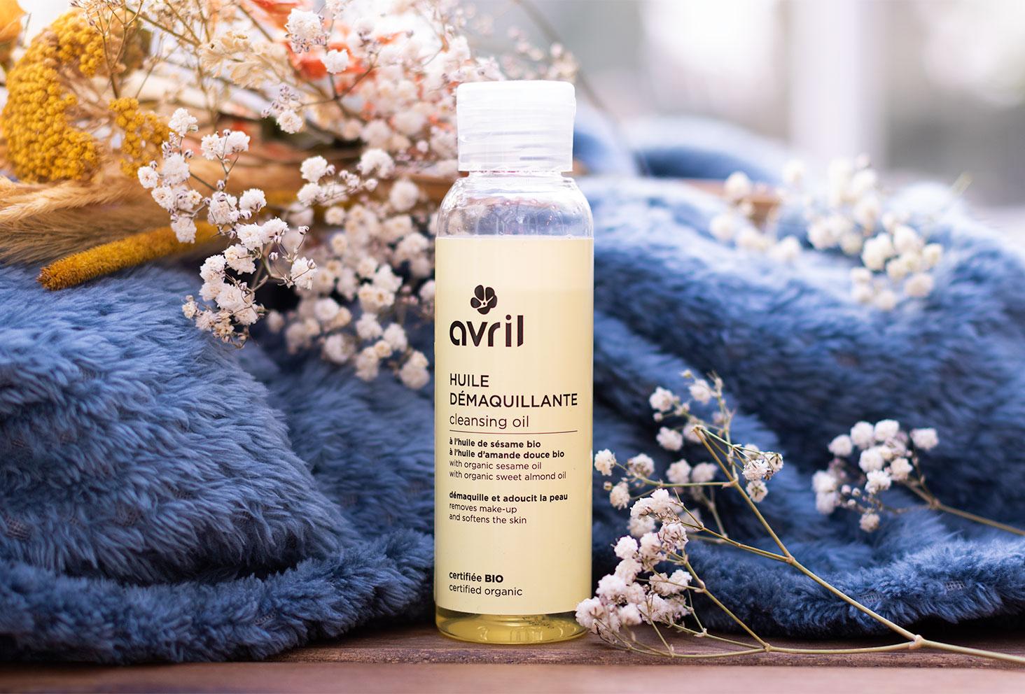 L'huile démaquillante Avril sur une table en bois, entourée de fleurs sèches et d'un énorme plaid bleu