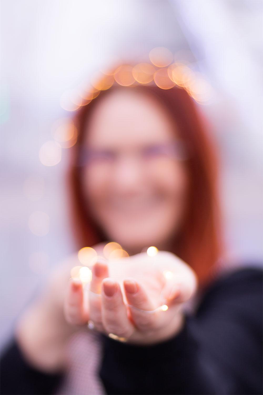 Jeux de lumière flous avec une guirlande lumineuse dans les mains