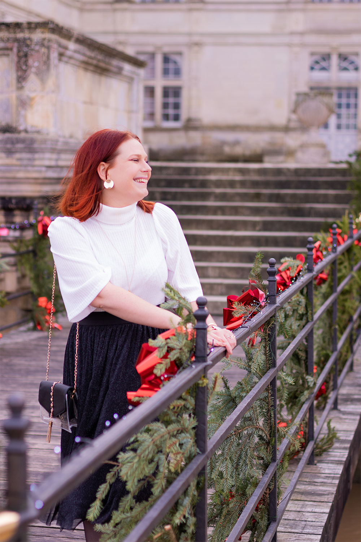 Accrochée au rambardes du pont en bois du château de Villandry décoré pour Noël, de profil la pochette à l'épaule, en pull blanc et jupe midi noire