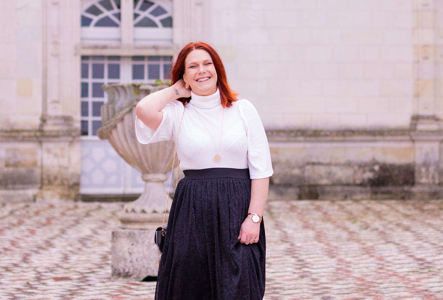 En pull blanc à col roulé et jupe en tulle noire à paillettes, la main dans la nuque un médaillon autour du coup, dans la cour du château de Villandry