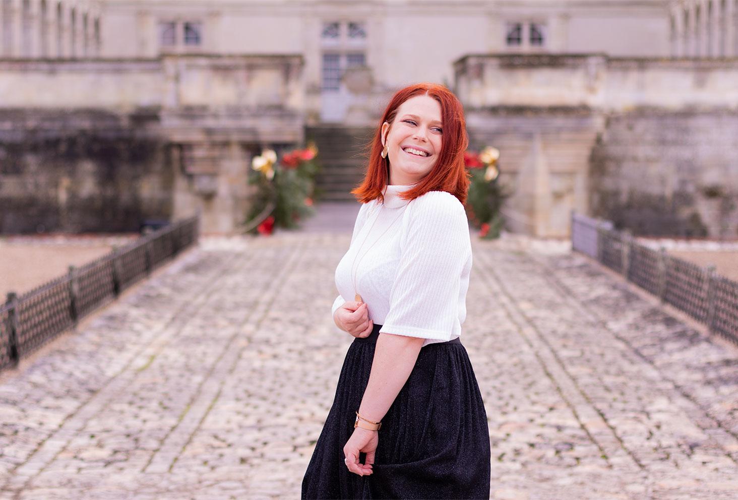 De profil dans la cour du château de Villandry, le sourire aux lèvres et la main tenant le côté de la jupe tutu noire, en col roulé blanc