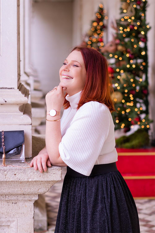 Accoudée au mur du château de Villandry devant le sapin lumineux, n pull col roulé blanc et jupe à paillettes noire, une montre dorée au poignet la main sous le menton