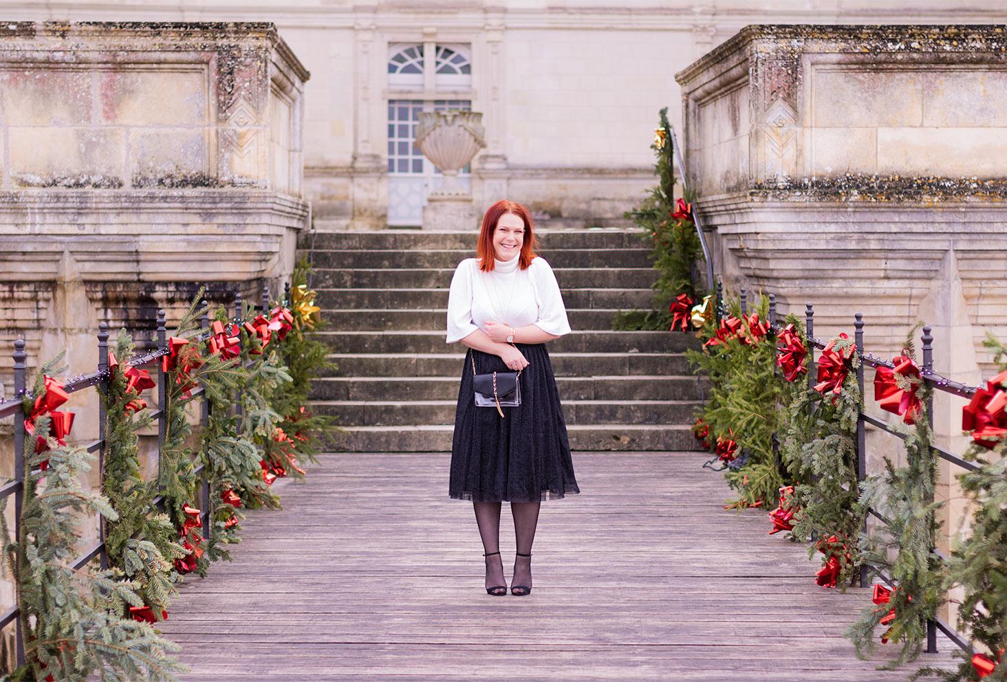 Sur le pont en bois décoré pour Noël au château de Villandry, en jupe tutu noire et pull blanc à col haut