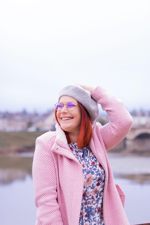 Assise sur une rambarde devant le pont du château d'Amboise, la mains sur le béret gris et en manteau rose